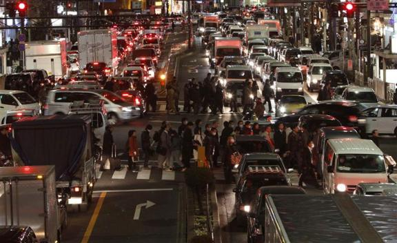 Traffic is in chaos as people are forced to walk home between grid locked vehicles in central Tokyo