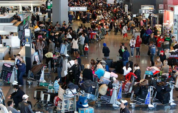 Passengers crowd as they queue to check in for flights at Narita airport in Narita